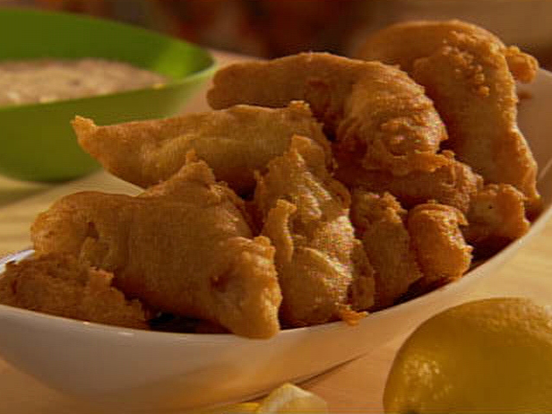 Several pieces of fried catfish filets placed in a plain white boat shaped dish