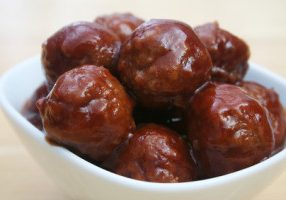 Close  up of glazed meatballs in a white bowl
