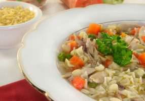 a chicken soup with shell pasta and vegetables